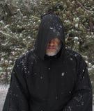 Άτομο που φορά ένα μαύρο με κουκούλα χιόνι ακρωτηρίων που πέφτει κανένα μάτι Στοκ Εικόνα
