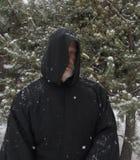 Άτομο που φορά μια μαύρη με κουκούλα πτώση χιονιού ακρωτηρίων Στοκ Φωτογραφία
