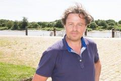 άτομο που φορά τα μπλε ενδύματα που θέτουν στο τοπίο θάλασσας το μεσαιωνικό χωριό της Ευρώπης στοκ φωτογραφία