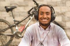 Άτομο που φορά την άσπρη κόκκινη συνεδρίαση επιχειρησιακών πουκάμισων κάτω, ακουστικά στο κεφάλι, που απολαμβάνει τη μουσική που  Στοκ Φωτογραφία