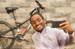 Άτομο που φορά την άσπρη κόκκινη συνεδρίαση επιχειρησιακών πουκάμισων κάτω, να κρατήσει ψηλά το κινητό τηλέφωνο που παίρνει selfi Στοκ εικόνα με δικαίωμα ελεύθερης χρήσης