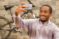 Άτομο που φορά την άσπρη κόκκινη συνεδρίαση επιχειρησιακών πουκάμισων κάτω, να κρατήσει ψηλά το κινητό τηλέφωνο που παίρνει selfi Στοκ φωτογραφίες με δικαίωμα ελεύθερης χρήσης