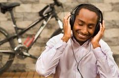 Άτομο που φορά την άσπρη κόκκινη συνεδρίαση επιχειρησιακών πουκάμισων κάτω με τα ακουστικά επάνω, που απολαμβάνουν τη μουσική χαμ Στοκ Εικόνες