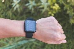 Άτομο που φορά τη σειρά 3 ΠΣΤ ρολογιών της Apple με το τηλέφωνο App Στοκ φωτογραφία με δικαίωμα ελεύθερης χρήσης