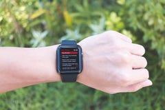 Άτομο που φορά τη σειρά 3 ΠΣΤ ρολογιών της Apple με το BBC App Στοκ Εικόνες