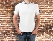 Άτομο που φορά το άσπρο πουκάμισο στο υπόβαθρο τούβλου Στοκ Εικόνες