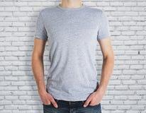 Άτομο που φορά το γκρίζο πουκάμισο στο υπόβαθρο τούβλου Στοκ Εικόνες