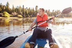 Άτομο που φορά το καγιάκ κωπηλασίας συντηρητικών ζωής στη λίμνη Στοκ φωτογραφία με δικαίωμα ελεύθερης χρήσης