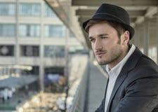 Άτομο που φορά το καπέλο και που φαίνεται έξω παράθυρο Στοκ Εικόνες