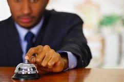 Άτομο που φορά το κομψό μπλε κουδούνι γραφείων κοστουμιών πιέζοντας στην υποδοχή ξενοδοχείων Στοκ Εικόνες