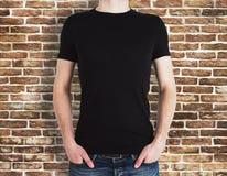 Άτομο που φορά το μαύρο πουκάμισο στο υπόβαθρο τούβλου Στοκ φωτογραφία με δικαίωμα ελεύθερης χρήσης