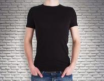 Άτομο που φορά το μαύρο πουκάμισο στο υπόβαθρο τούβλου Στοκ Εικόνες
