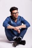 Άτομο που φορά το πουκάμισο τζιν και τα γυαλιά, κάθισμα Στοκ Εικόνες