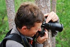 Άτομο που φωτογραφίζει από πίσω από το δέντρο. Στοκ Φωτογραφίες
