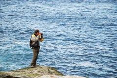 Άτομο που φωτογραφίζει ενάντια στην μπλε θάλασσα Στοκ εικόνα με δικαίωμα ελεύθερης χρήσης