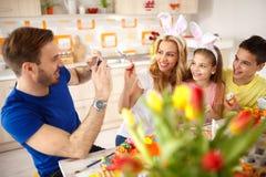 Άτομο που φωτογραφίζει την οικογένεια χρωματίζοντας τα αυγά στοκ εικόνα