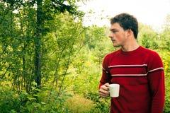 Νεαρός άνδρας στη φύση με μια κούπα του καφέ Στοκ Φωτογραφίες