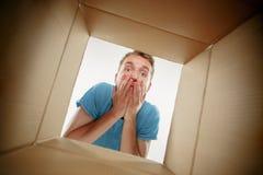 Άτομο που χαμογελά, να ανοίξει και ανοίγματος κιβώτιο χαρτοκιβωτίων και κοίταγμα μέσα στοκ φωτογραφία με δικαίωμα ελεύθερης χρήσης