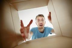 Άτομο που χαμογελά, να ανοίξει και ανοίγματος κιβώτιο χαρτοκιβωτίων και κοίταγμα μέσα στοκ φωτογραφία