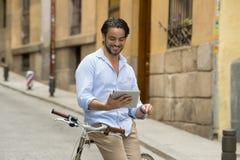 Άτομο που χαμογελά χρησιμοποιώντας Διαδίκτυο με το ψηφιακό μαξιλάρι ταμπλετών στο εκλεκτής ποιότητας δροσερό αναδρομικό ποδήλατο Στοκ Φωτογραφίες