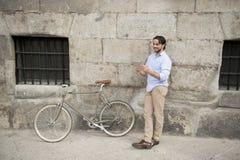 Άτομο που χαμογελά χρησιμοποιώντας Διαδίκτυο με το ψηφιακό μαξιλάρι ταμπλετών στο εκλεκτής ποιότητας δροσερό αναδρομικό ποδήλατο Στοκ Φωτογραφία
