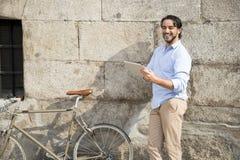 Άτομο που χαμογελά χρησιμοποιώντας Διαδίκτυο με το ψηφιακό μαξιλάρι ταμπλετών στο εκλεκτής ποιότητας δροσερό αναδρομικό ποδήλατο Στοκ φωτογραφίες με δικαίωμα ελεύθερης χρήσης