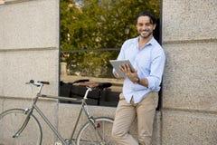 Άτομο που χαμογελά χρησιμοποιώντας Διαδίκτυο με το ψηφιακό μαξιλάρι ταμπλετών στο εκλεκτής ποιότητας δροσερό αναδρομικό ποδήλατο Στοκ φωτογραφία με δικαίωμα ελεύθερης χρήσης