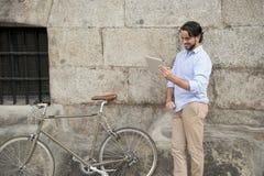 Άτομο που χαμογελά χρησιμοποιώντας Διαδίκτυο με το ψηφιακό μαξιλάρι ταμπλετών στο εκλεκτής ποιότητας δροσερό αναδρομικό ποδήλατο Στοκ Εικόνες