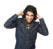 Άτομο που χαμογελά και που κρατά το περιλαίμιο σακακιών τζιν στοκ εικόνες