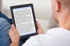 Άτομο που χαλαρώνει στο σπίτι να διαβάσει ένα eBook on-line Στοκ Εικόνες