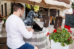 Άτομο που χρησιμοποιεί έναν σύγχρονο φορητό υπολογιστή σε έναν υπαίθριο πίνακα Στοκ φωτογραφία με δικαίωμα ελεύθερης χρήσης