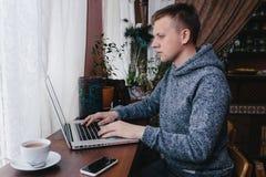 Άτομο που χρησιμοποιεί ένα lap-top και ένα κινητό τηλέφωνο σε έναν καφέ Νεαρός άνδρας που πίνει το γ Στοκ Εικόνα