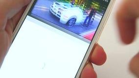 Άτομο που χρησιμοποιεί ένα Smartphone για να δει το βίντεο σε Youtube απόθεμα βίντεο