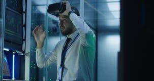 Άτομο που χρησιμοποιεί τα γυαλιά και το lap-top VR στο κέντρο δεδομένων απόθεμα βίντεο