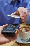 Άτομο που χρησιμοποιεί την ανέπαφη πληρωμή App στο κινητό τηλέφωνο στον καφέ Στοκ εικόνες με δικαίωμα ελεύθερης χρήσης