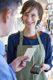 Άτομο που χρησιμοποιεί την ανέπαφη πληρωμή App στο κινητό τηλέφωνο στο κατάστημα Στοκ φωτογραφία με δικαίωμα ελεύθερης χρήσης