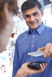 Άτομο που χρησιμοποιεί την ανέπαφη πληρωμή App στο κινητό τηλέφωνο στο κατάστημα Στοκ Εικόνα