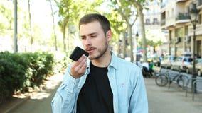 Άτομο που χρησιμοποιεί την αναγνώριση φωνής στο τηλέφωνο για να καταγράψει ένα μήνυμα απόθεμα βίντεο