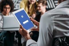 άτομο που χρησιμοποιεί την ταμπλέτα με το facebook app στην οθόνη με τους συνέταιρους του στοκ εικόνα