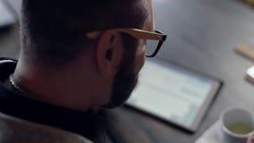 Άτομο που χρησιμοποιεί την ταμπλέτα στον πίνακα κοντά στο φλυτζάνι απόθεμα βίντεο