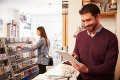 Άτομο που χρησιμοποιεί την ψηφιακή ταμπλέτα πίσω από το μετρητή σε ένα κατάστημα αρχείων Στοκ Εικόνες
