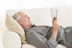 Άτομο που χρησιμοποιεί την ψηφιακή ταμπλέτα στον καναπέ στο σπίτι Στοκ φωτογραφία με δικαίωμα ελεύθερης χρήσης