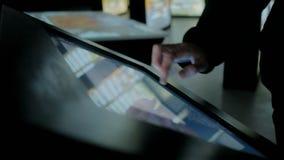 Άτομο που χρησιμοποιεί τη διαλογική επίδειξη οθονών επαφής στο μουσείο σύγχρονης ιστορίας απόθεμα βίντεο