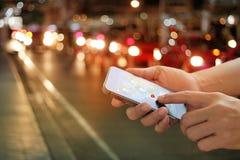 Άτομο που χρησιμοποιεί τη ναυσιπλοΐα app στο smartphone στην οδό τη νύχτα Στοκ Φωτογραφίες