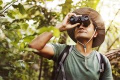 Άτομο που χρησιμοποιεί τις διόπτρες που προσέχουν τα πουλιά στη ζούγκλα Στοκ Εικόνες
