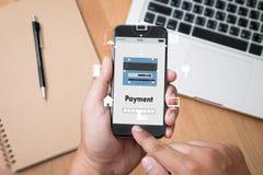 Άτομο που χρησιμοποιεί τις κινητές πληρωμές σε απευθείας σύνδεση ψωνίζοντας μ-καταθέτοντας σε τράπεζα Διαδίκτυο Gl Στοκ Φωτογραφία
