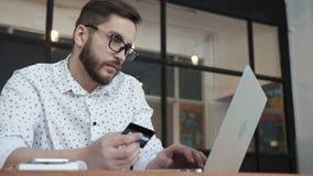 Άτομο που χρησιμοποιεί τις σε απευθείας σύνδεση τραπεζικές εργασίες με το lap-top και την κάρτα απόθεμα βίντεο