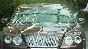 Άτομο που χρησιμοποιεί τον εξοπλισμό πλυσίματος αυτοκινήτων για να καθαρίσει την πολυτέλεια αυτόματη, προετοιμάζοντας το όχημα γι φιλμ μικρού μήκους