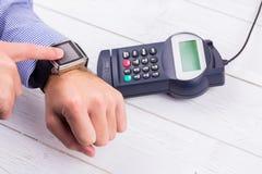 Άτομο που χρησιμοποιεί το έξυπνο ρολόι για να εκφράσει την αμοιβή στοκ φωτογραφία