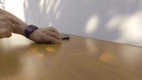 Άτομο που χρησιμοποιεί το έξυπνο ρολόι του και το έξυπνο τηλέφωνό του απόθεμα βίντεο